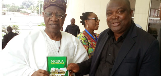 Alhaji Lai Mohammed, Minister of Information and Culture receiving a copy of Lucky George's  Guide Book, Nigeria: A Holiday Guide.